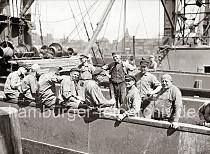 """640_0228 Pause der Arbeiter auf einem Frachter - die Hafenarbeiter sitzen in der Sonne, einige rauchen, einer hat eine Flasche Bier in der Hand. Die meisten der Männer tragen einen """"Elbsegler"""", die typische Hamburger Schirmmütze mit Kordel. Die Aufgabe der sogen. Schauerleute besteht im Stauen bzw. dem Be- und Entladen der Frachschiffe. Der Begriff Schauermann stammt vom niederländischen Wort sjouwen = schleppen. Die Arbeiter im Hafen Hamburgs waren zumeist Tagelöhner, die zur Erledigung einer konkreten Arbeit eingestellt wurden."""